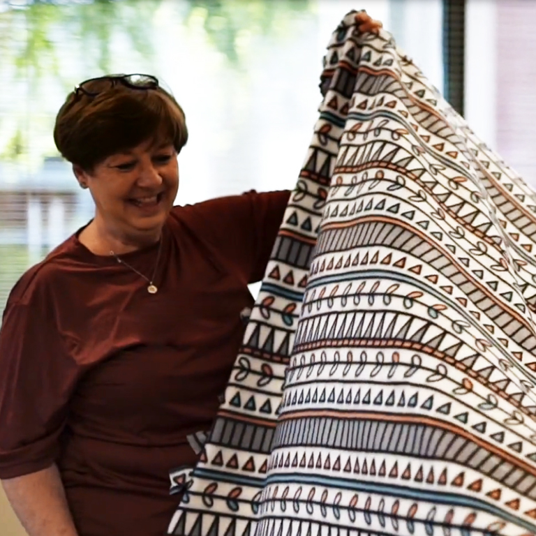 Volunteers hold a blanket created through Project Linus